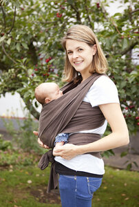 Portrait of young woman carrying baby girl in baby sling - MFRF000313