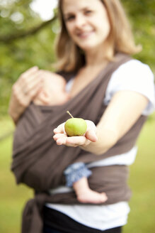 Mother with baby girl holding apple in her hand - MFRF000318