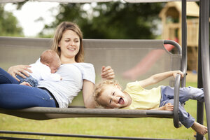 Portrait of little girl with her mother and little sister on a canopy swing - MFRF000328