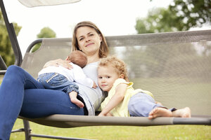 Portrait of happy young mother with her two little daughters on a canopy swing - MFRF000330