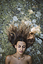 Portrait of a woman with closed eyes lying on a rock with tousled hair - RAEF000266
