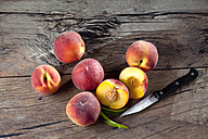 Whole and sliced peaches and a kitchen knife on wood - CSF025962