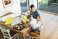 Father and daughter at home using sewing machine - UUF005122