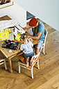 Father and daughter at home using sewing machine - UUF005125