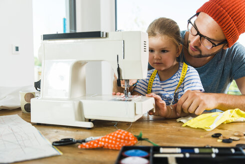 Father and daughter at home using sewing machine - UUF005134