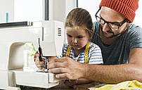 Father and daughter at home using sewing machine - UUF005135