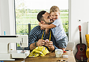 Happy daughter cuddling father at home - UUF005144