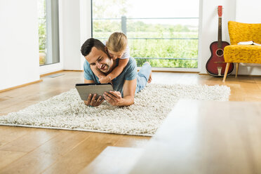 Happy father and daughter lying on rug using digital tablet - UUF005157