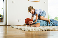 Daughter kneeling on father's back lying on floor - UUF005164