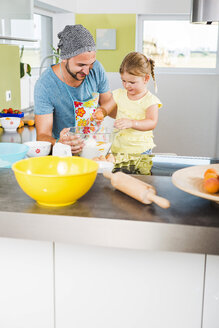 Father and daughter baking in kitchen - UUF005167