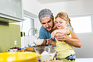 Father and daughter baking in kitchen - UUF005169