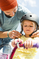 Father closing daughter's helmet on bike - UUF005186