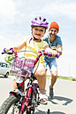 Father accompanying daughter on bike - UUF005193