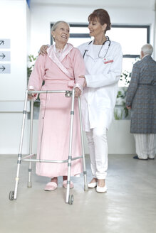 Doctor leading elderly patient with walking frame on hospital floor - ZEF007237