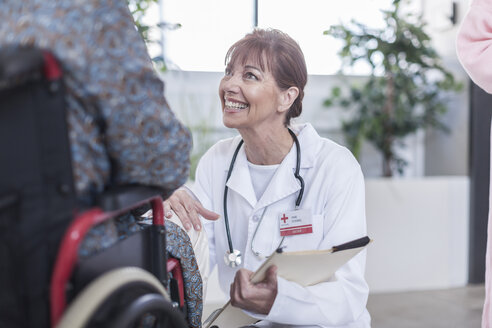 Doctor smiling at patient in wheelchair - ZEF007248
