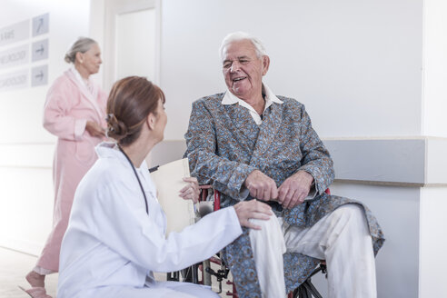 Doctor and smiling elderly patient in wheelchair - ZEF007249