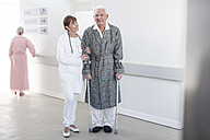 Doctor leading elderly patient with crutches on hospital floor - ZEF007252