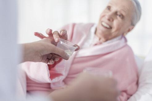 Patient lying in hospital bed receiving medication - ZEF007263