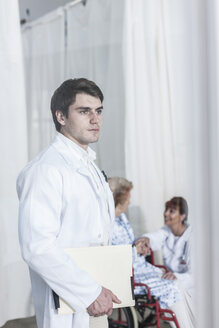 Serious doctor holding file with doctor and patient in background - ZEF007274