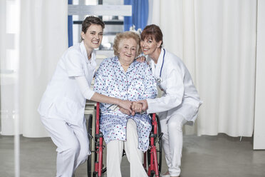 Doctor and nurse caring for elderly patient in wheelchair - ZEF007276