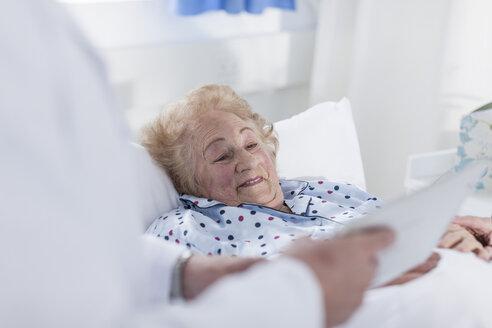 Doctor showing digital tablet to elderly patient in hospital bed - ZEF007277