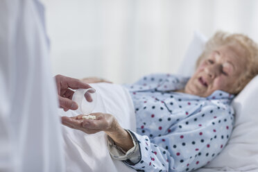 Patient lying in hospital bed receiving medication - ZEF007279