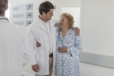 Doctor embracing elderly patient on hospital floor - ZEF007283