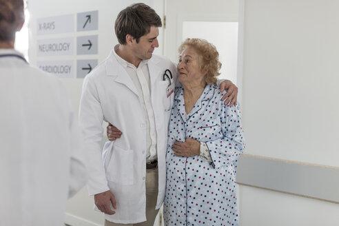 Doctor embracing elderly patient on hospital floor - ZEF007283