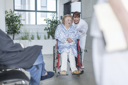 Doctor with elderly patient in wheelchair on hospital floor - ZEF007291