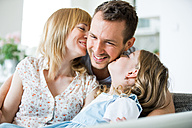 Happy family sitting on couch, mother and daughter kissing father - WESTF021496