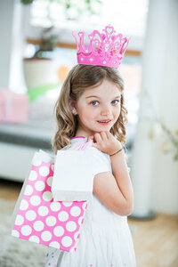 Girl wearing pink crown carrying gift bags - WESTF021559