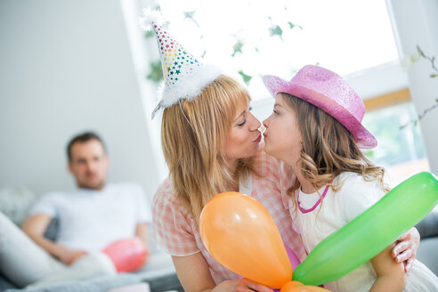 Family celebrating with balloons and party hats - WESTF021577