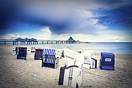 Germany, Heringsdorf, view to sea bridge with hooded beach chairs on the beach in the foreground - PUF000395