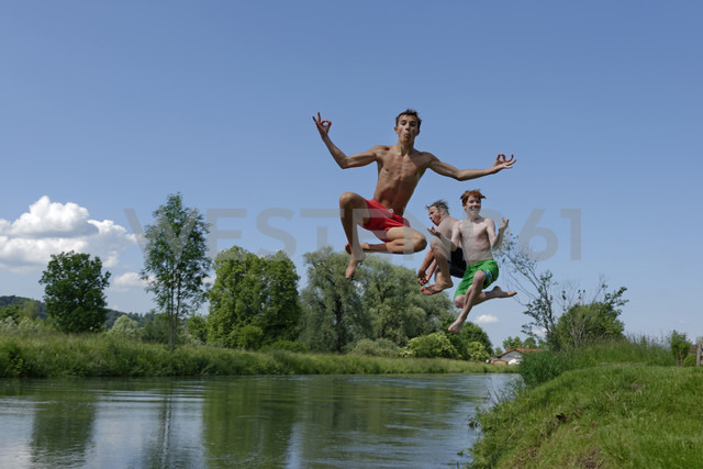 Germany, Bavaria, two teenage boys and man jumping into River Loisach - LBF001167 - Lisa und Wilfried Bahnmüller/Westend61