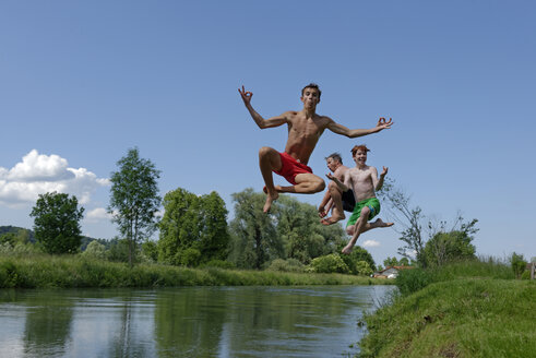 Germany, Bavaria, two teenage boys and man jumping into River Loisach - LBF001167