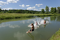 Germany, Bavaria, kids and man jumping into River Loisach - LBF001170