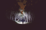 Silhouette of a man standing on forest track at night illuminating the woods with a flashlight - RAE000241