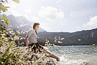 Germany, Bavaria, Eibsee, smiling woman splashing in water - RBF003005