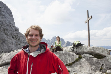 Germany, Bavaria, Osterfelderkopf, portrait of smiling hiker with woman at summit cross - RBF003017