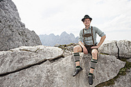 Germany, Bavaria, Osterfelderkopf, man in traditional clothes sitting in mountain landscape - RBF003024
