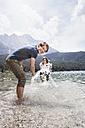 Germany, Bavaria, Eibsee, playful couple splashing in water - RBF003043