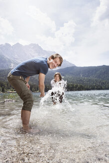 Germany, Bavaria, Eibsee, playful couple splashing in water - RBF003043