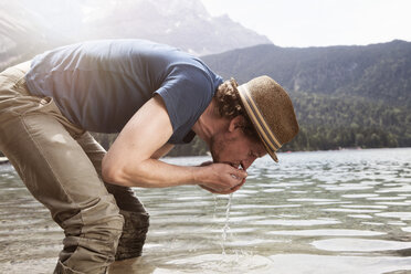 Germany, Bavaria, Eibsee, man drinking water from lake - RBF003046