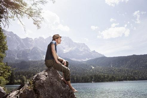 Germany, Bavaria, Eibsee, man sitting on rock on lakeshore - RBF003048