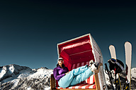 Austria, Altenmarkt-Zauchensee, skier sitting in hooded beach chair in the mountains - HHF005359
