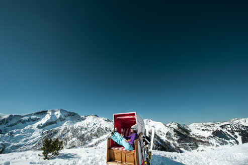 Austria, Altenmarkt-Zauchensee, skier sitting in hooded beach chair in the mountains - HHF005365