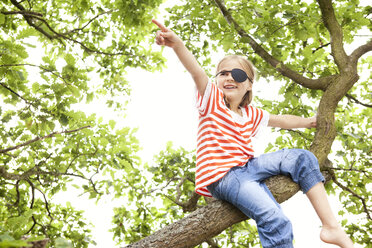 Girl dressed up as pirate sitting on a tree pointing finger - MFRF000282