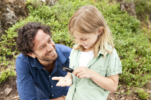 Girl with father looking through magnifying glass - MFRF000273