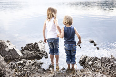 Boy and girl standing hand in hand at lakeshore - MFRF000269