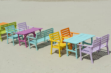 Corsica, Calvi, colorful tables and benches at beach - LBF001159